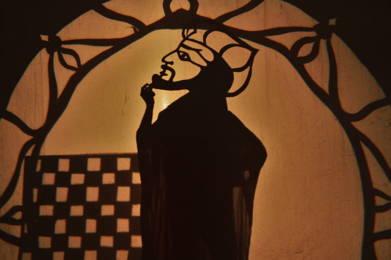 A drawing of a man against a window backdrop in the traditional Arab Puppet Theatre style