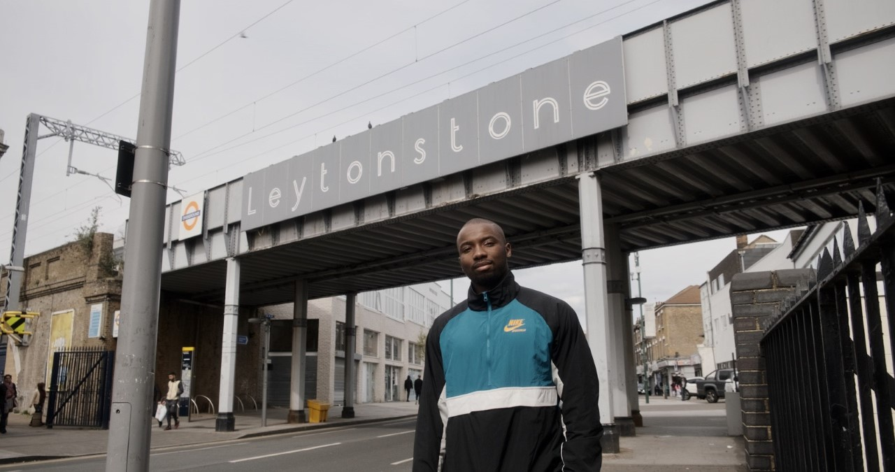 A man dressed in a blue white and black tracksuit jacket stands in front of a sign that says Leytonstone