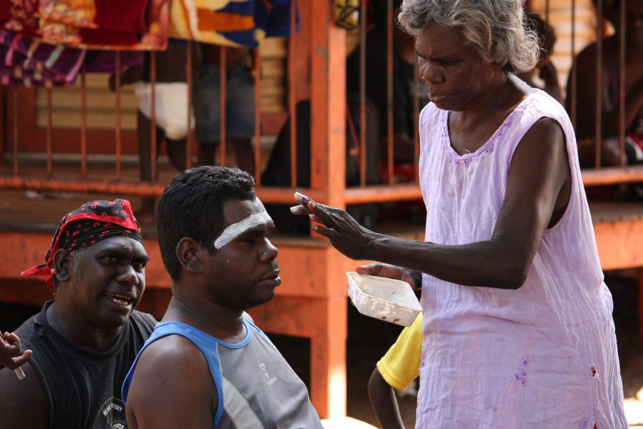A woman paints a mans face in an act of traditional body decoration