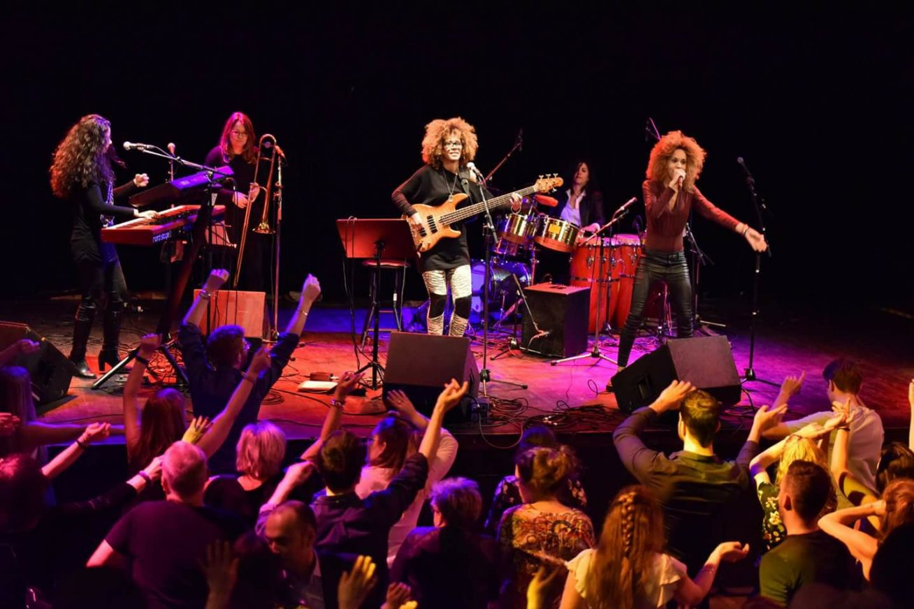 An all-female band perform on stage as a crowd dances along