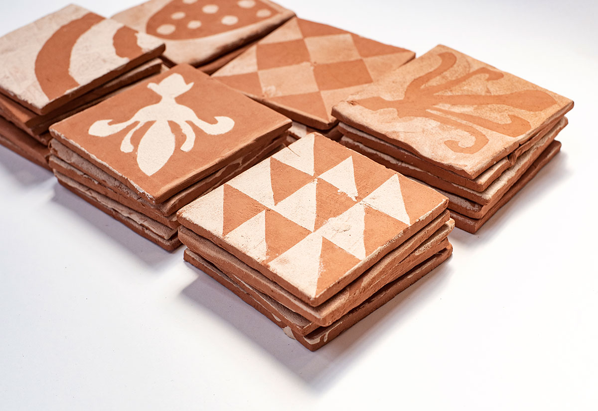 Terracotta style tiles with white patterns on them