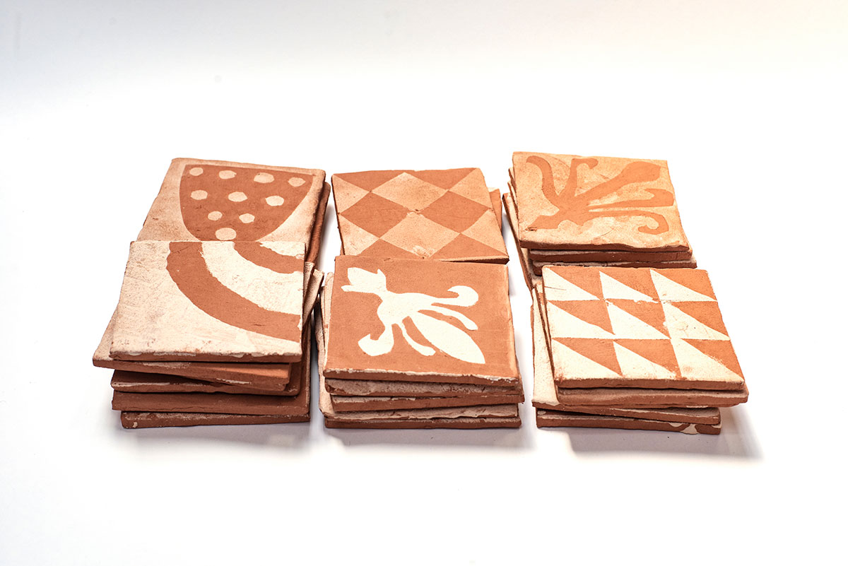 Terracotta tiles with white patterns, made by children at local primary schools