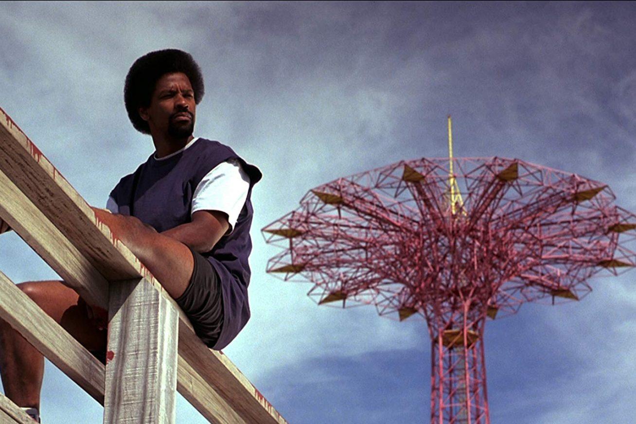 He Got Game - Actor Denzel Washington sits on a wooden bridge