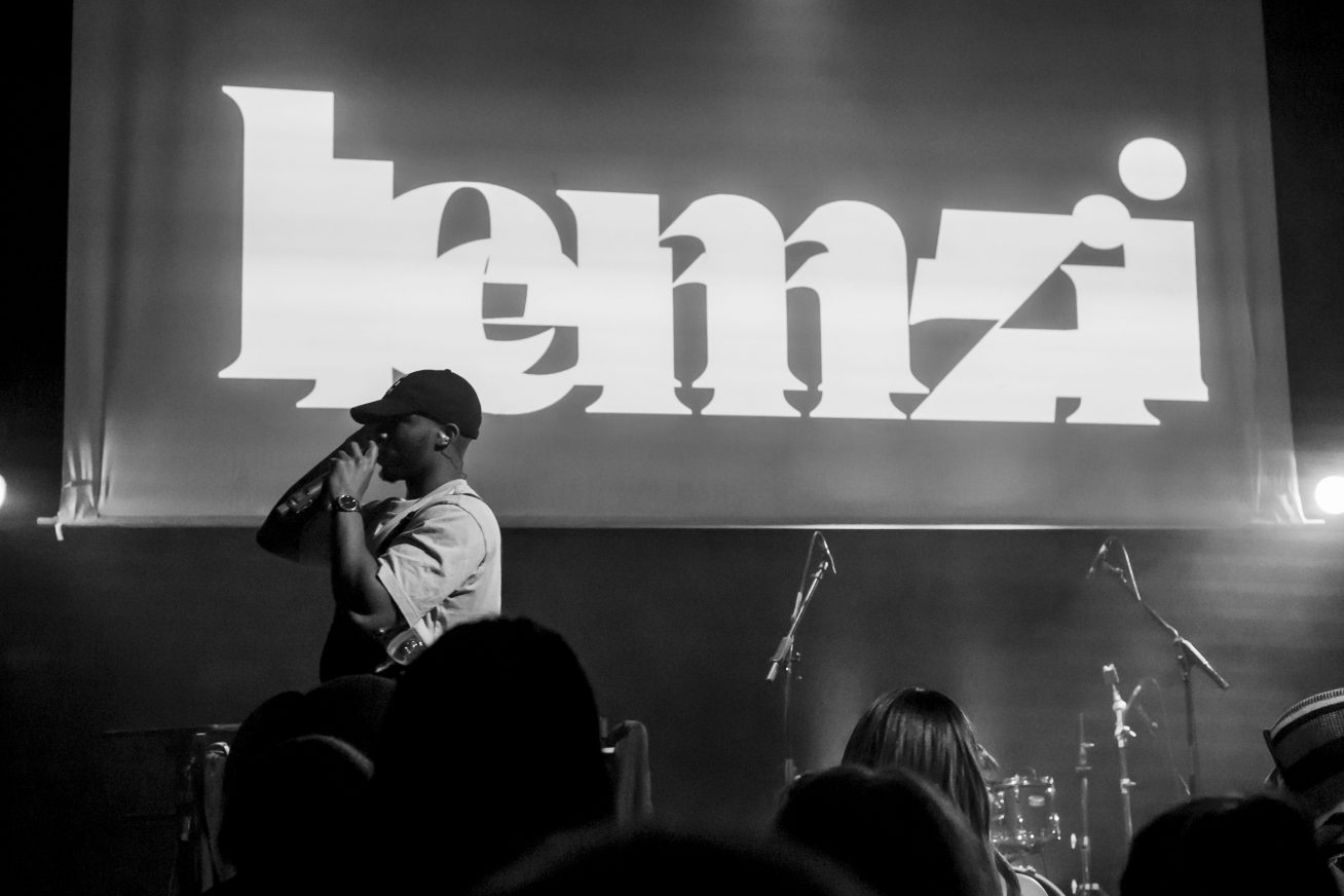 A man in a white t-shirt and black cap stands on stage with a microphone, in front of a screen that says LEMZI