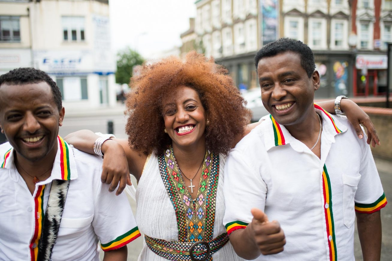 A woman and two men smile into the camera as they pose on a street dressed in white