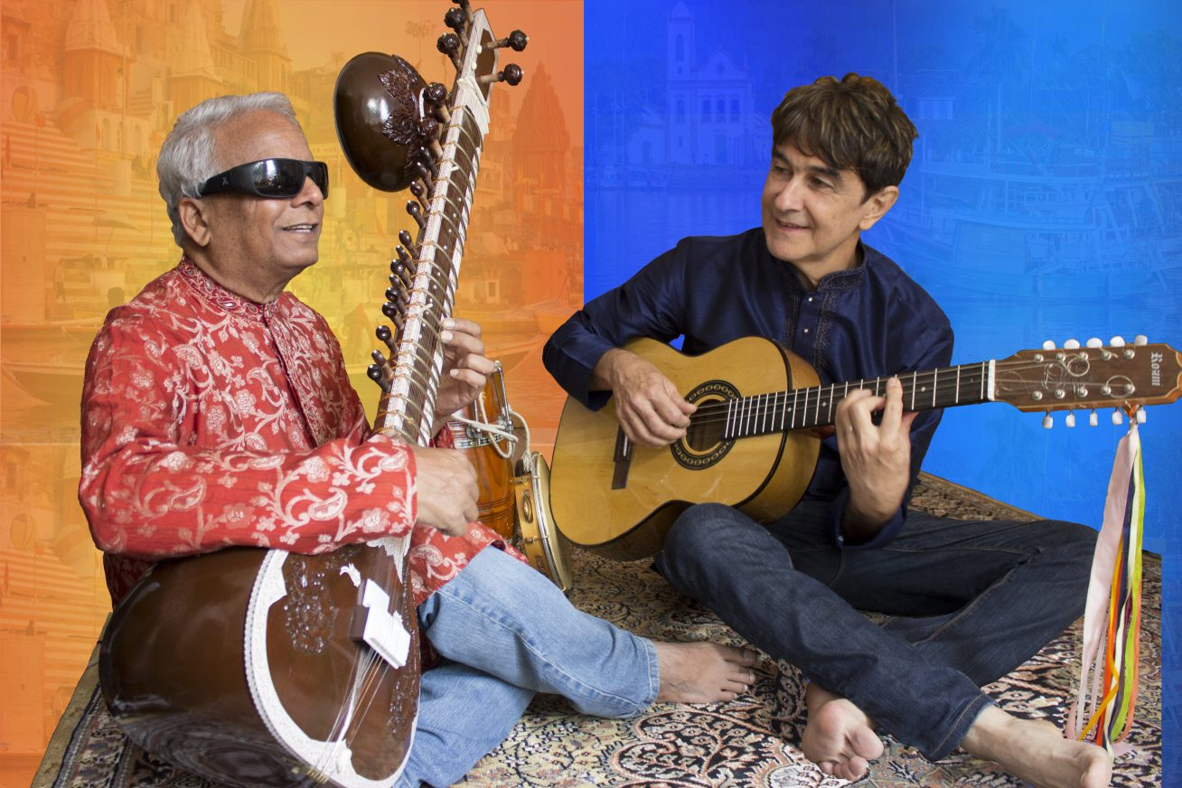 Two musicians - Gui Tavares and Baluji Shiravastav - play side by side on stage