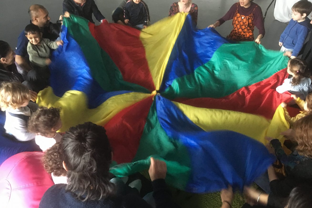 Children and adults play together with a rainbow coloured parachute