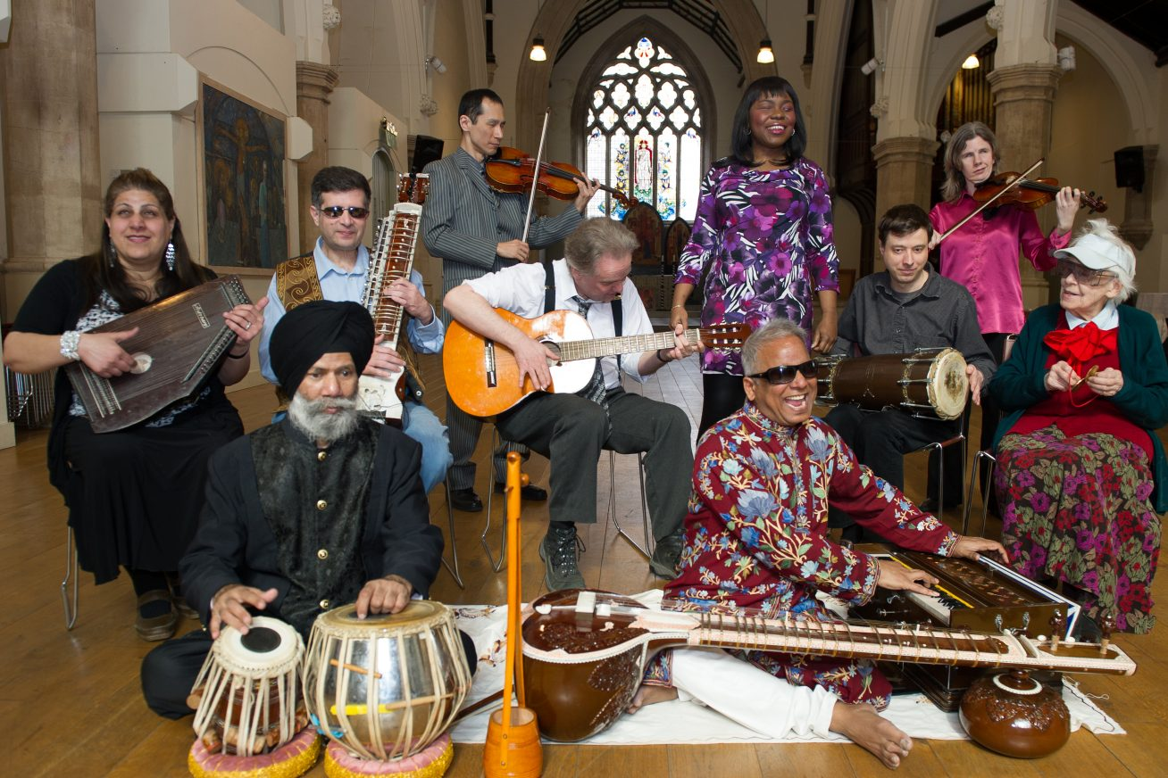 A group of musicians pose together with their instruments