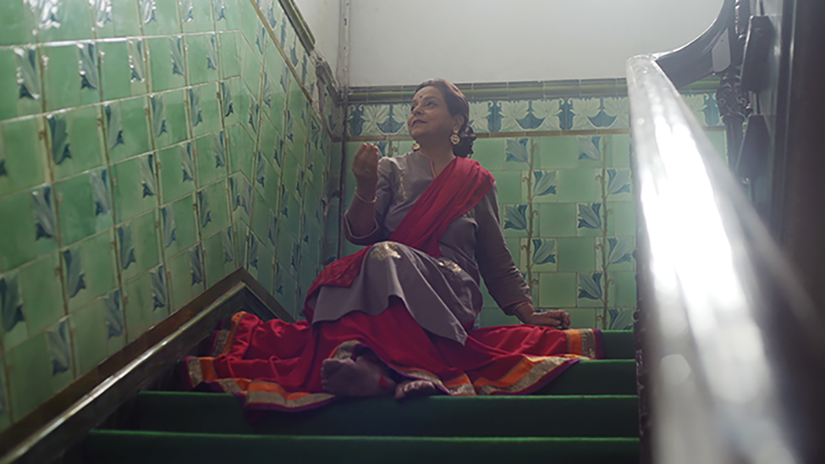 a woman dressed in traditional south-east asian clothing sits in a stairwell