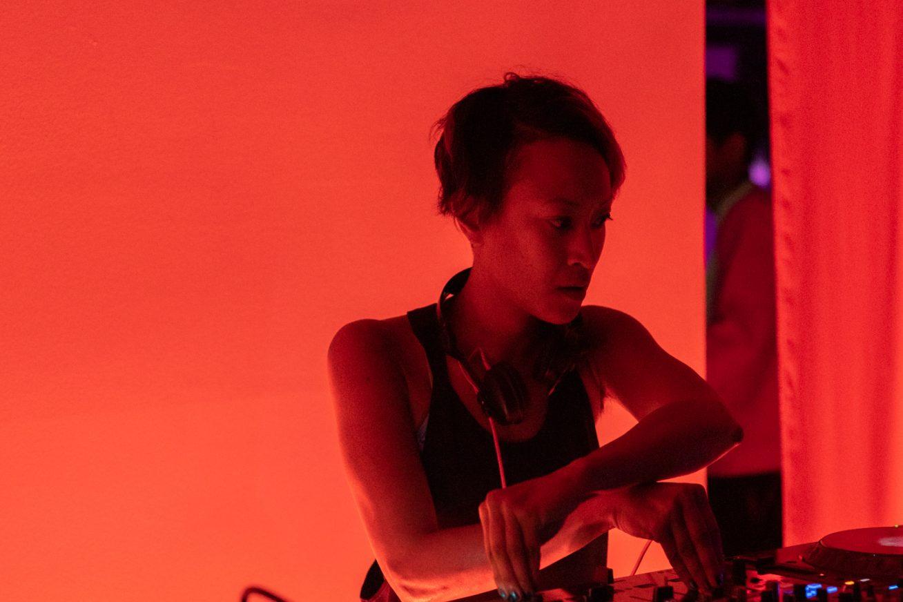 DJ illuminated by orange light