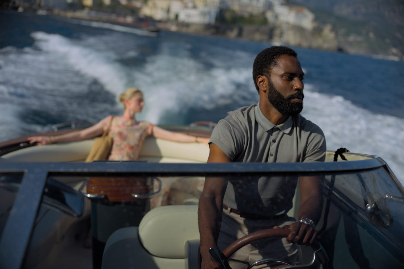 John David Washington driving a speedboat with Elizabeth Debick sitting in the back