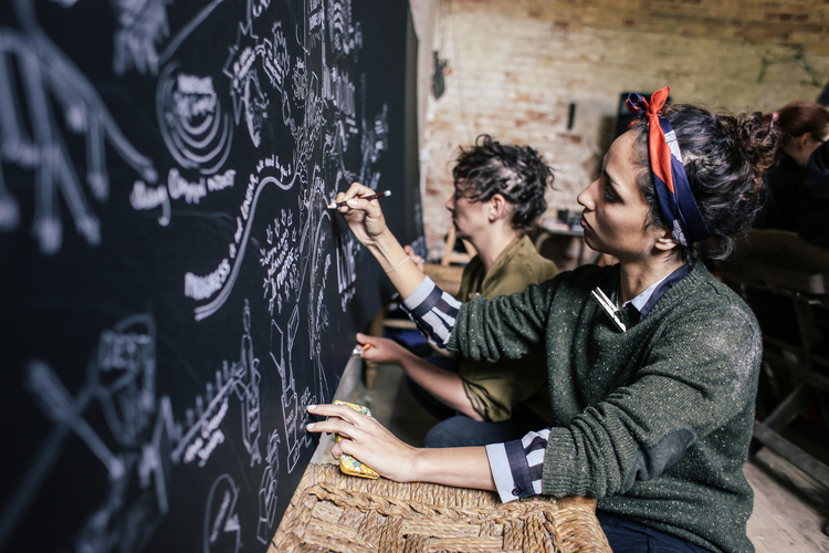people adding their drawings to a black board
