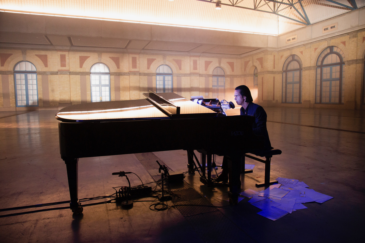 Nick Cave sat at a black grand piano within the beautifully up-lit Alexandra Palace