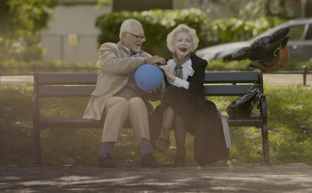 an older woman and a man playing with a balloon